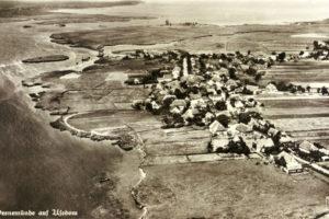 Luftbildaufnahme des Fischerdorfes Peenemünde mit Blickrichtung Nordwest, im Hintergrund links das Fischerdorf Freest, mittig die Peenemünder Schanze, Reproduktion einer Postkarte, die im Original auf der Rückseite einen schriftlichen Kartengruß enthält und auf den 16.04.1937 datiert ist (HTM Peenemünde, Archiv)