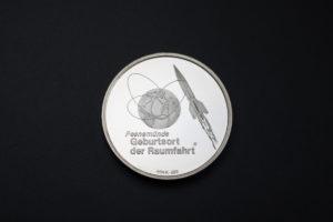 """Vorderseite der Gedenkmedaille """"Peenemünde. Geburtsort der Raumfahrt"""" in Silber aus dem Jahr 1992. Sie wurde im Auftrag des Historisch-Technischen Informationszentrums Peenemünde (HTI) durch das Mecklenburger Münzkontor hergestellt. Die Münzen und andere """"Repräsentationsgeschenke"""" hätten anlässlich der Jubiläumsfeier, zu der es letztlich nicht kam, verschenkt und verkauft werden sollen. (HTM Peenemünde, Archiv)"""