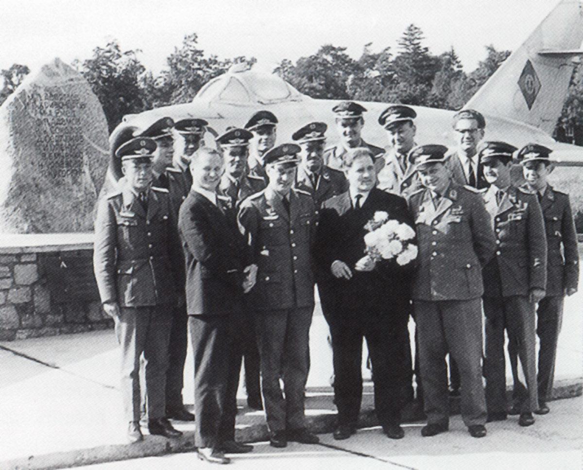 Dewjatajew mit Angehörigen der NVA in der Dienststelle des Jagdfliegergeschwaders 9 in Karlshagen, im Hintergrund der Gedenkstein in Erinnerung an die Flucht Dewjatajews und eine MIG 17 (HTM Peenemünde, Archiv)