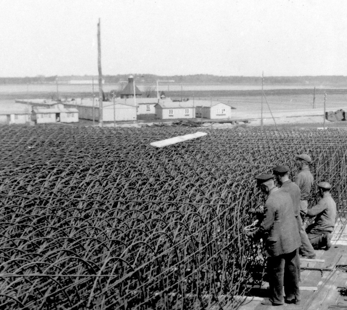Während des Baus der Schaltwarte des Kraftwerks ist im Hintergrund die Kapelle Peenemünde inmitten der wenigen noch verbliebenen Gebäude des ursprünglichen Dorfes zu sehen. Foto: Josef Greiner, Mai 1941 (HTM Peenemünde, Archiv)